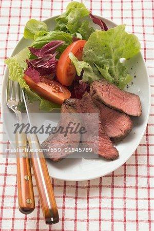 Sliced beef steak with salad