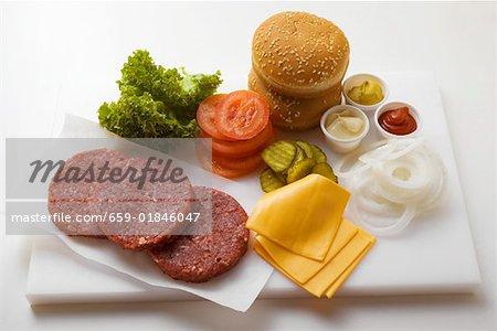 Zutaten für Cheeseburger auf Schneidebrett