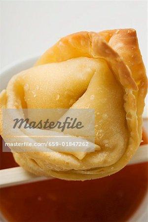 Un wonton frit avec sauce aigre-douce (gros plan)