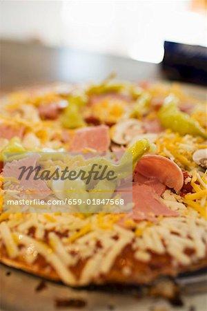 Pizza au jambon, champignons, poivrons et fromage