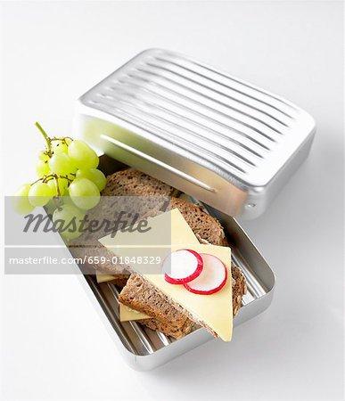 Käse-Sandwiches und grüne Trauben in der Lunch-box