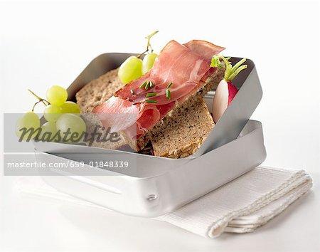Schinken-Sandwiches, Radieschen und Trauben in der Lunch-box
