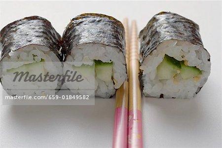 Three maki sushi with cucumber and chopsticks