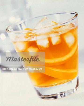 Un verre de jus d'orange avec des cubes de glace et de tranches d'orange