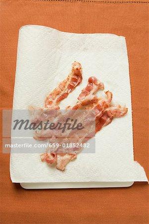 Gebratene Speckscheiben Speck auf saugfähigem Küchenpapier