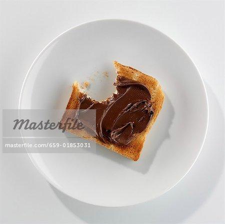 Eine Scheibe Toast mit Nutella, einen Bissen genommen, auf einem Teller