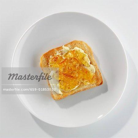 Eine Scheibe Toast mit Butter und Marmelade auf einem Teller
