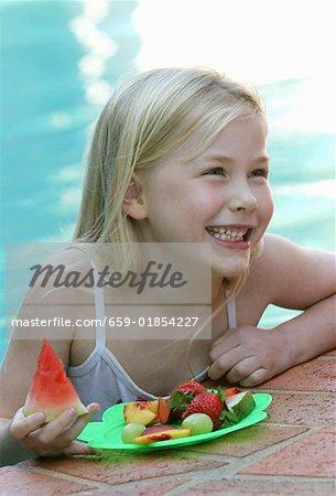 Petite fille avec des fruits frais à la piscine