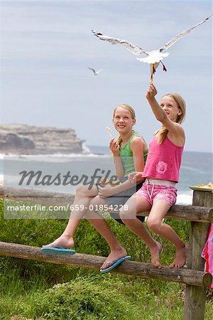 Deux filles, nourrir les puces une mouette sur la plage
