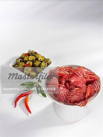 Tranches de salami, olives vertes et piments