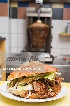 Un döner kebab avec de la viande sur la broche en arrière-plan