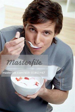 Quark jeune homme manger avec fraises fraîches