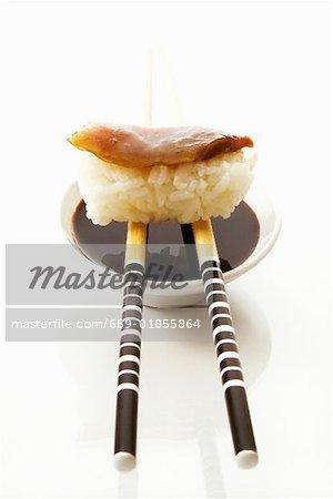 Nigiri sushi on chopsticks on small bowl of soy sauce