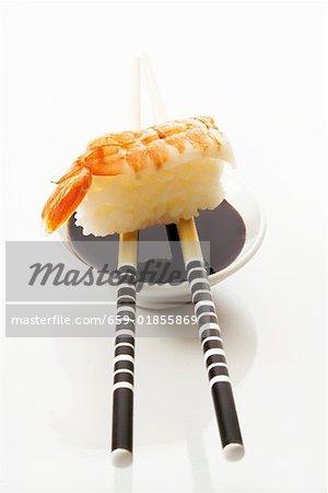 Shrimp nigiri sushi with soy sauce and chopsticks