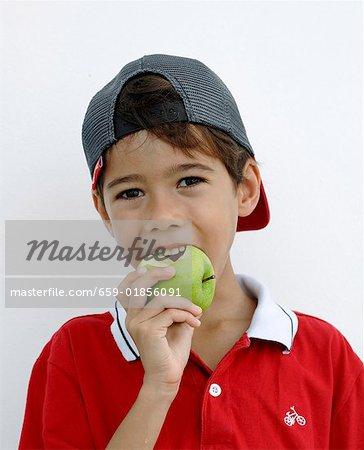 Garçon de mordre dans une pomme