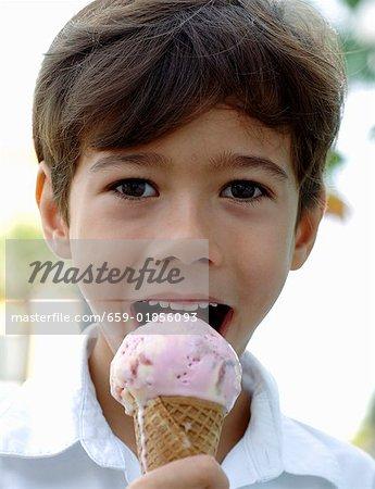 Boy eating strawberry and vanilla ice cream cone