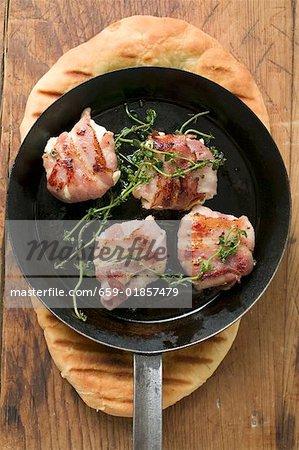 Fromage de chèvre au bacon dans une poêle à frire sur pain plat