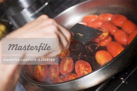 Turning tomatoes in frying pan