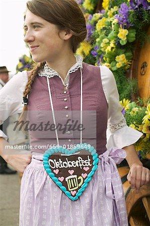 Woman in national dress with Lebkuchen heart at Oktoberfest
