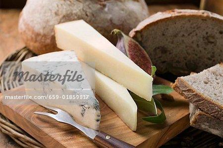 Différents types de fromage, de pain et de la moitié d'un figuier
