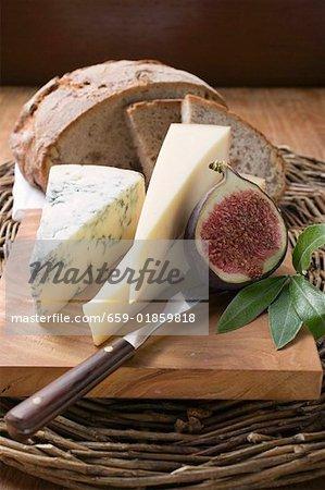Différents types de fromage, de pain et de la moitié de la figue