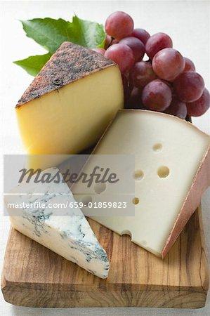 Différents types de fromage et raisins rouges
