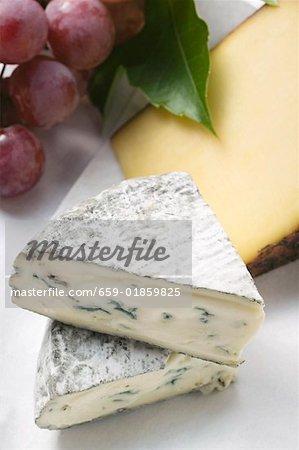 Deux différents types de fromage et raisins rouges