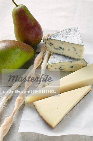Différents types de fromage, poires fraîches et grissini