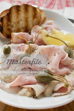 Porc rôti froid avec câpres, citron et pain grillé