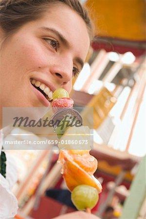 Woman holding skewered candied fruit (Oktoberfest, Munich)