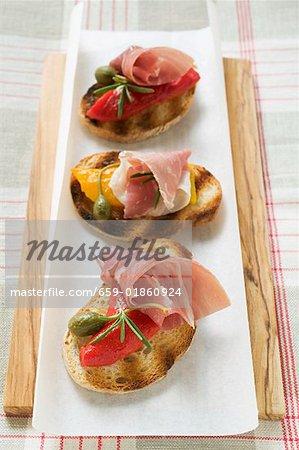 Plusieurs crostini avec jambon cru, poivrons et câpres géants