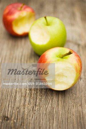 Trois pommes avec piqûres prises sur fond en bois