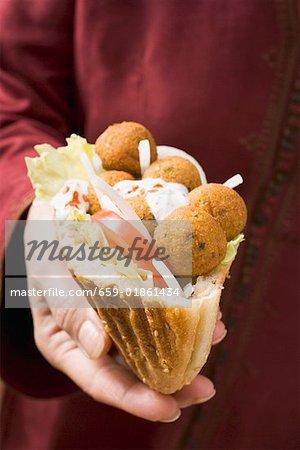 Frau hält Fladenbrot gefüllt mit Falafel (Küken-Erbse-Bälle)