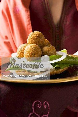 Frau servieren Falafel (Bälle Küken-Phenylethylamin) mit Gemüse