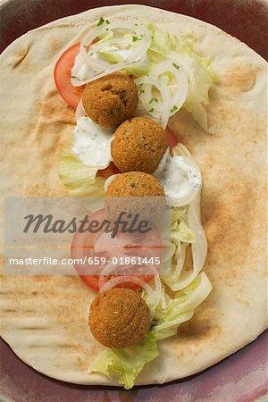 Falafel (boulettes de pois chiche) avec des légumes sur pain plat