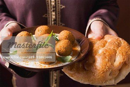 Woman serving falafel (chick-pea balls) with flatbread