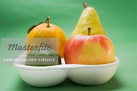 Orange, poire, citron vert et pomme dans une barquette en polystyrène