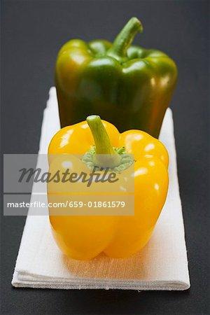 Deux poivrons (jaune, vert) sur toile de lin blanc