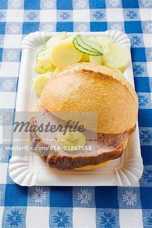 Leberk0se in roll with mustard & potato salad on paper plate
