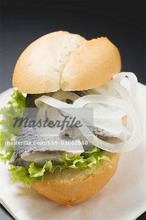 Brötchen mit Hering und Zwiebeln auf Papier Serviette gefüllt