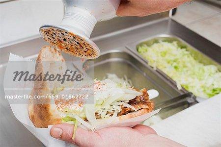 Sprinkling seasoning on a döner kebab (opened)