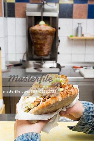 Mains tenant un döner kebab dans un snack-bar
