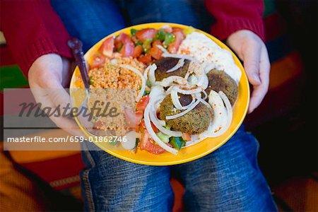 Person, die Falafel mit Beilagen (Nordafrika)