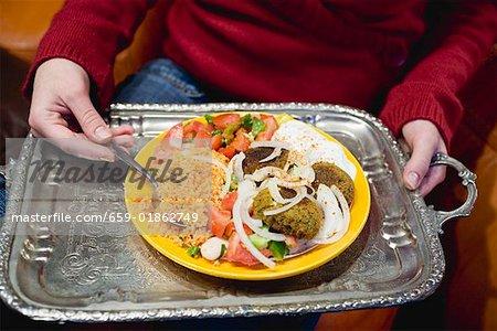 Person, die Falafel mit Begleitungen auf Tablett (Nordafrika)