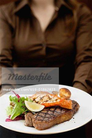 Femme tenant la planche de Surf & Turf (steak de bœuf avec crevettes)