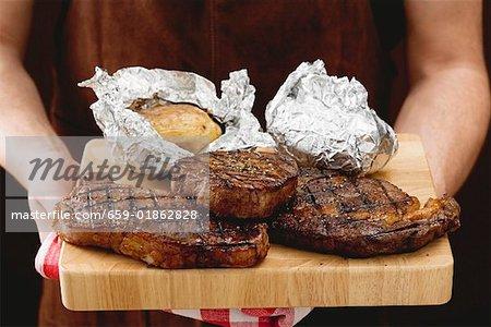Homme tenant des steaks de bœuf grillé sur planche à découper