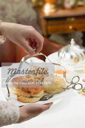 Mains servant des pâtisseries sucrées et scones pour manger avec du thé