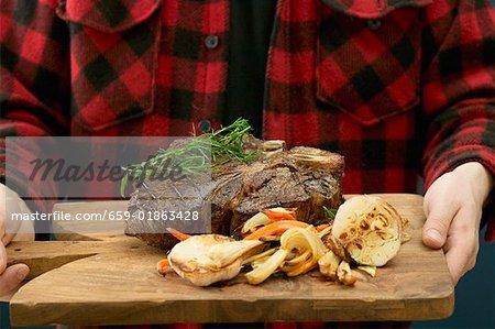 Homme qui dessert grillé t-bone steak sur planche à découper