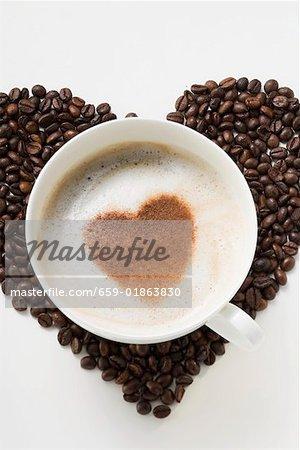 Tasse de cappuccino avec cœur de poudre de cacao sur les grains de café