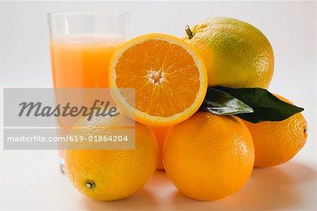 Verre de jus d'orange et plusieurs oranges